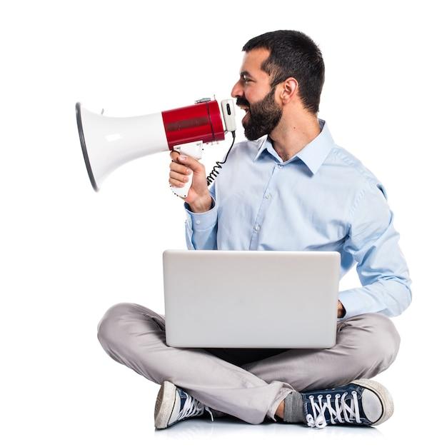Homme avec un ordinateur portable criant par mégaphone Photo gratuit
