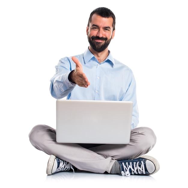 Un homme avec un ordinateur portable faisant un accord Photo gratuit