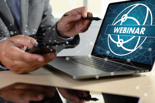 Homme avec ordinateur portable montrant le webinaire à l'écran Photo Premium