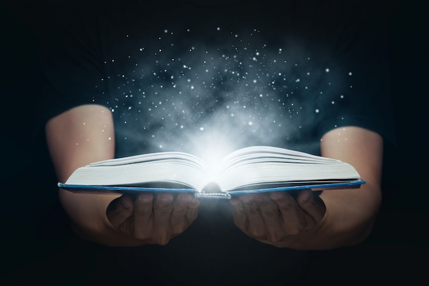 L'homme A Ouvert Un Livre Magique Avec Des Lumières Croissantes Et De La Poudre Magique. Concept D'apprentissage Et D'éducation Photo Premium