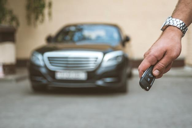 L'homme ouvre la voiture avec un porte-clés, à l'arrière-plan, une voiture noire. Photo Premium