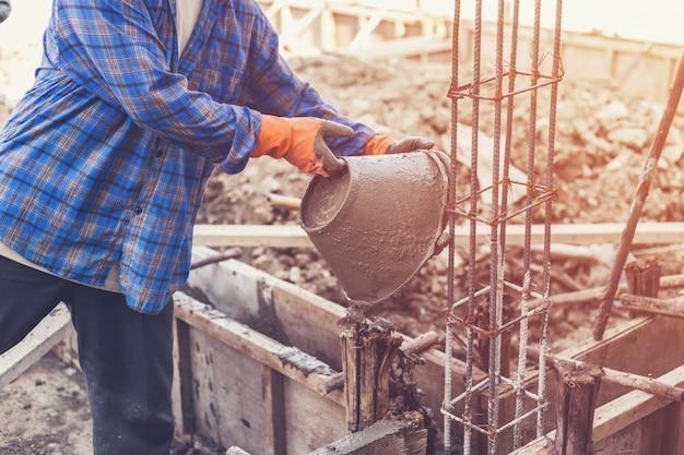 Homme ouvrier mélange de mortier de mortier de ciment pour la construction avec un ton vintage. Photo Premium
