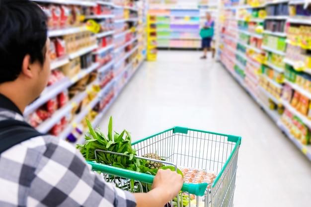 Homme avec panier d'achat de nourriture dans un supermarché. closeup détail du panier. Photo Premium