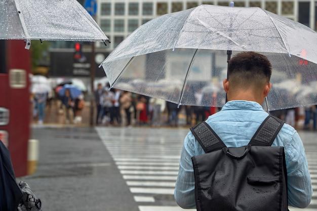 Homme avec parapluie marche Photo Premium