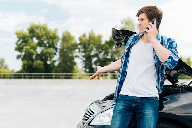 Homme parlant au téléphone avec espace de copie Photo gratuit