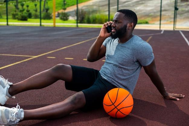 Homme parlant au téléphone sur un terrain de basket Photo gratuit