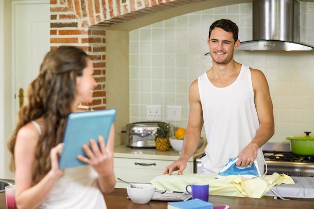 Homme parlant à une femme en repassant une chemise dans la cuisine Photo Premium