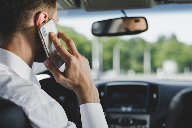 L'homme parle sur smartphone en conduisant la voiture Photo gratuit