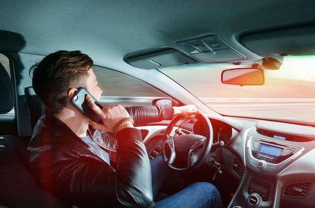 Un homme parle sur un téléphone portable dans une voiture Photo Premium