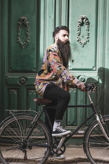 Homme passant sur la porte ancienne de vélo vert au soleil Photo gratuit