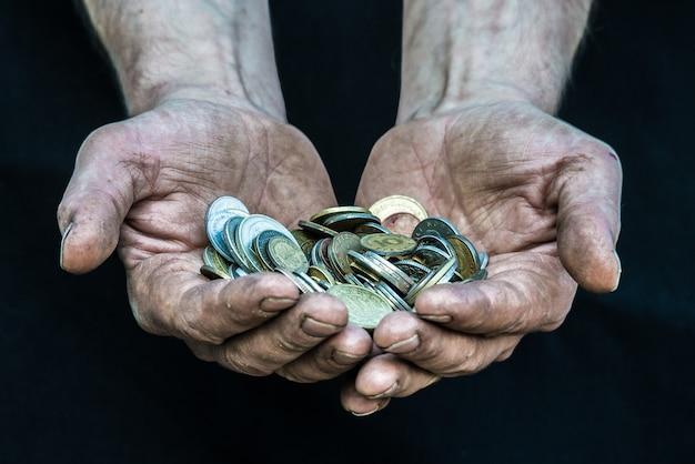 Homme Pauvre Sans-abri Avec De Nombreuses Pièces De Monnaie De Différents Pays Illustrant La Pauvreté Dans La Société Du Capitalisme Moderne Photo Premium