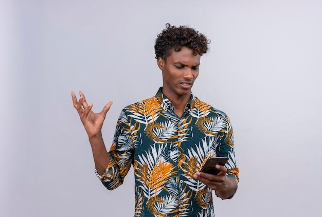Homme à La Peau Sombre En Colère Et Nerveux En Chemise Imprimée De Feuilles à La Recherche De Téléphone Mobile Et De Lever La Main Photo gratuit
