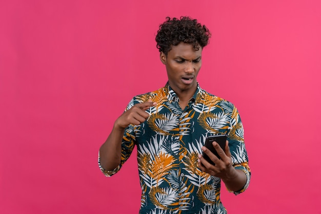 Homme à La Peau Sombre En Colère Et Nerveux En Chemise Imprimée De Feuilles à La Recherche De Téléphone Mobile Et Pointant Avec L'index Photo gratuit