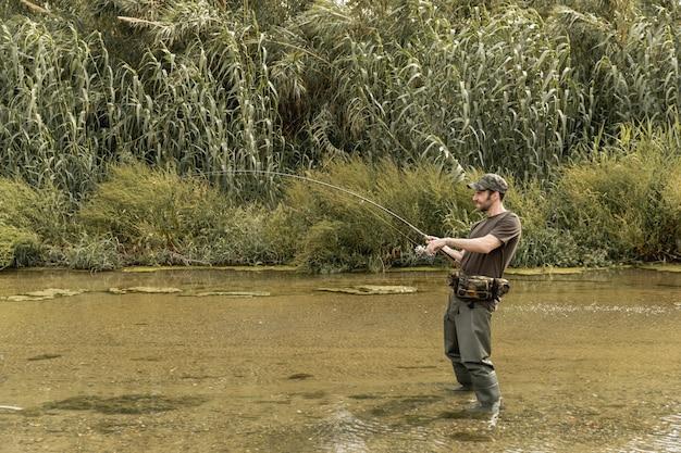 Homme pêchant à la rivière Photo gratuit