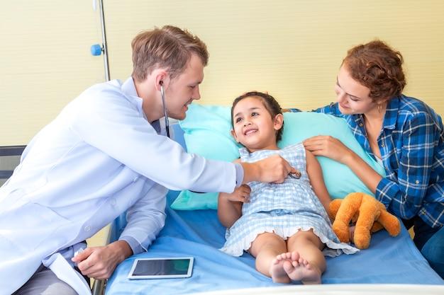Homme De Pédiatre (médecin) Examine Le Patient De Petite Fille à L'aide D'un Stéthoscope Sur L'hôpital De La Chambre à Coucher. Photo Premium