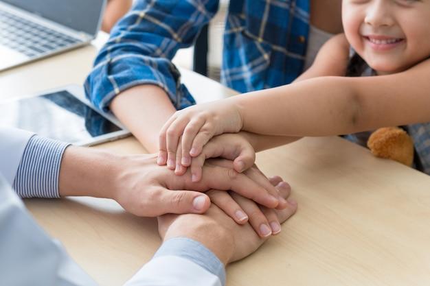 Homme pédiatre (médecin) joignant les mains pour rassurer et discuter de l'enfant à la chirurgie. Photo Premium