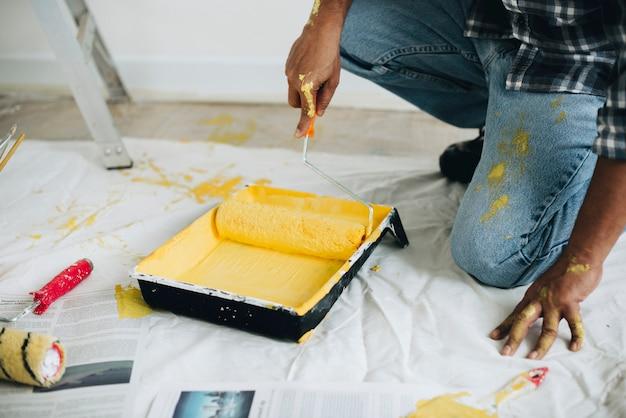 Homme peignant les murs jaune Photo gratuit