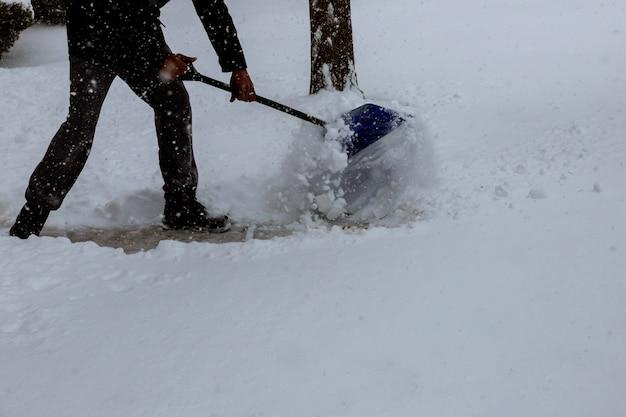 Un homme pellette de la neige sur le trottoir devant sa maison après une forte chute de neige Photo Premium