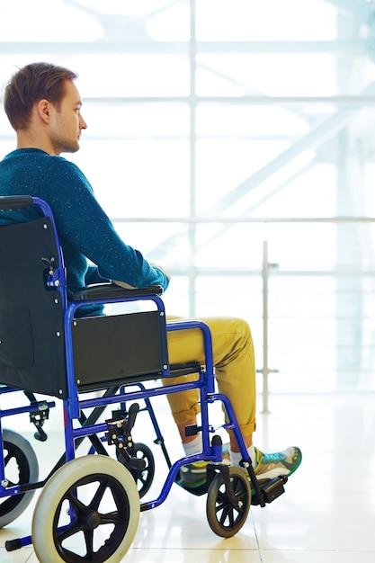 Homme pensif en fauteuil roulant Photo gratuit