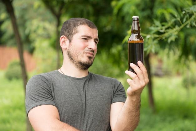 Homme pensif regardant bière Photo gratuit
