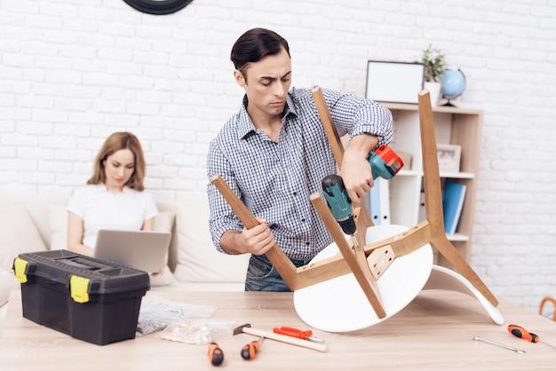 Homme avec une perceuse dans les mains, réparer la chaise dans la chambre. Photo Premium
