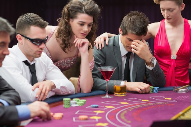 Homme perdant à la table de poker avec une femme le réconfortant Photo Premium