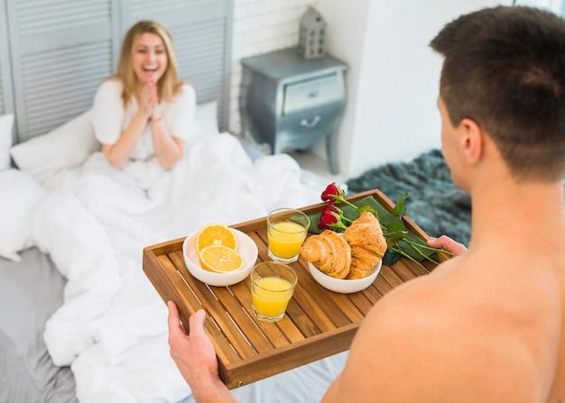 Homme avec petit-déjeuner à bord près d'une femme heureuse au lit Photo gratuit