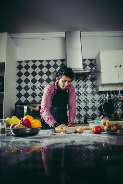 Homme, pétrir la pâte à pizza maison dans la cuisine. concept de cuisine Photo gratuit