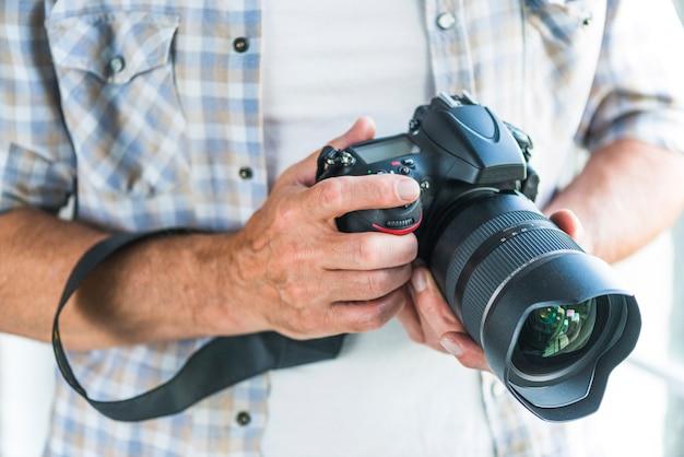 Homme photographe tenant l'appareil photo dslr en mains Photo gratuit