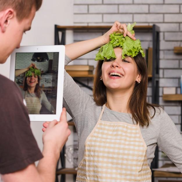 Homme photographiant une femme avec une feuille de salade sur la tête Photo gratuit