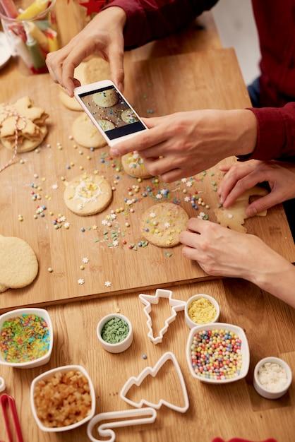 Homme Photographiant Ses Biscuits De Noël Photo gratuit