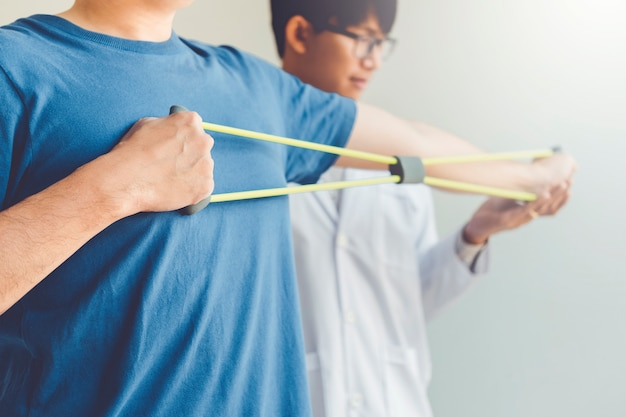 Homme de physiothérapeute donnant un traitement d'exercice avec une bande de résistance à propos du bras et de l'épaule d'un patient athlète Photo Premium