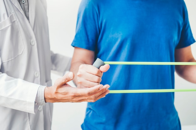 Homme de physiothérapeute donnant un traitement d'exercice avec une bande de résistance à propos des muscles de la poitrine et de l'épaule d'un patient athlète Photo Premium