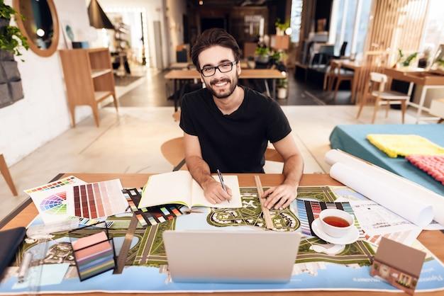 Homme pigiste prenant des notes sur un ordinateur portable assis au bureau. Photo Premium