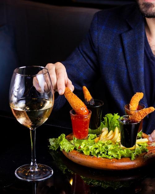 Homme Plongeant Les Crevettes Frites Dans Une Sauce Chili Douce Dans Un Verre à Liqueur Photo gratuit