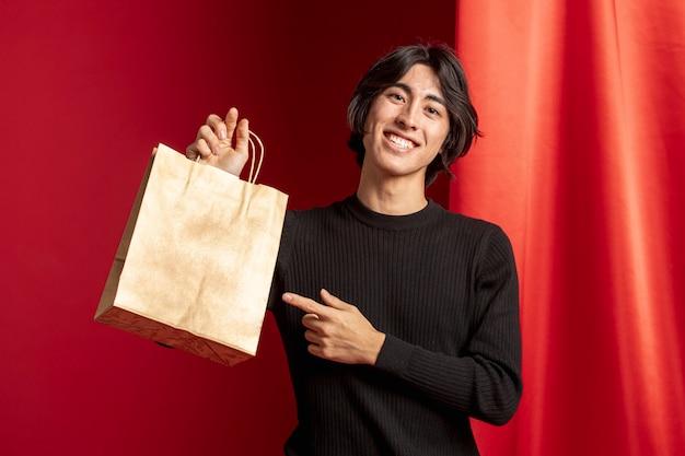 Homme pointant sur un sac pour le nouvel an chinois Photo gratuit