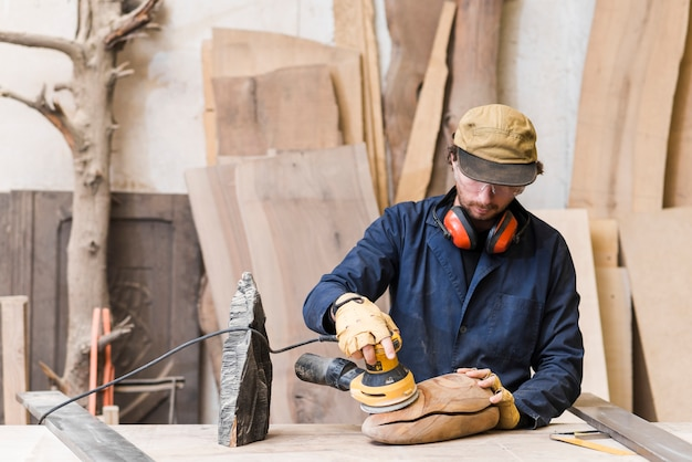 Homme ponçant un bois avec une ponceuse orbitale dans un atelier Photo gratuit