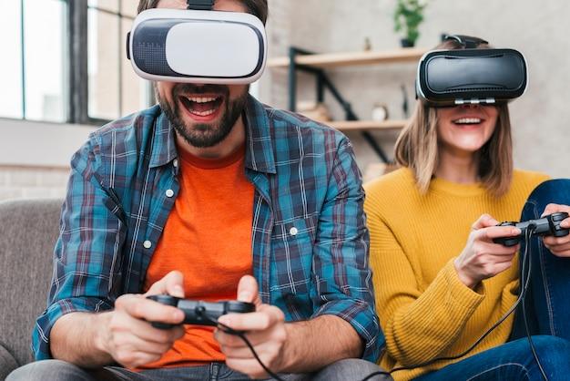 Homme portant des lunettes de réalité virtuelle jouant avec une manette de jeu Photo gratuit