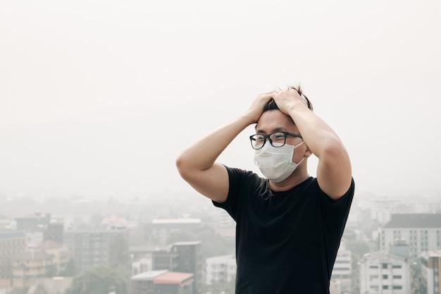 Homme portant un masque d'hygiène et malade à cause de la pollution de l'air en ville. Photo Premium
