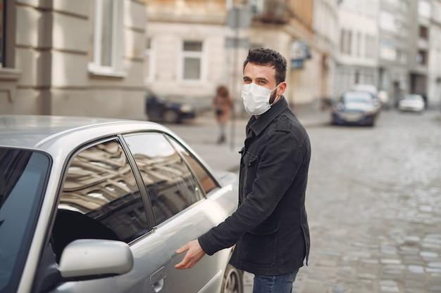 Homme Portant Un Masque De Protection Par Une Voiture Photo gratuit