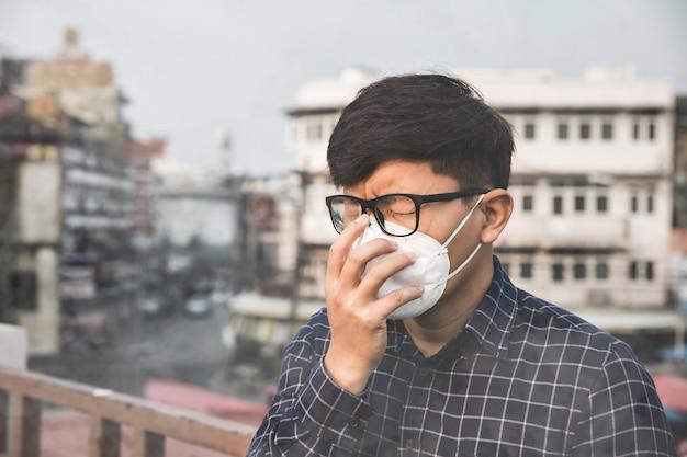 L'homme Portant Le Masque De Protection Respiratoire Contre La Pollution De L'air Et Les Particules De Poussière Dépasse Les Limites De Sécurité. Concept De Santé, Environnement, écologie. Photo Premium