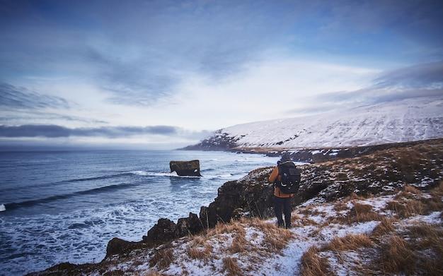 Homme Portant Un Sac à Dos Et Une Veste Debout Sur La Colline Enneigée Tout En Prenant Une Photo De La Mer Photo gratuit
