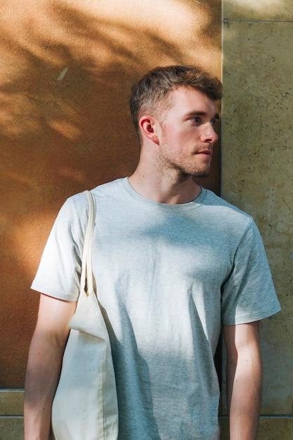 Homme portant un sac en tissu et debout près du mur à la recherche de suite Photo gratuit