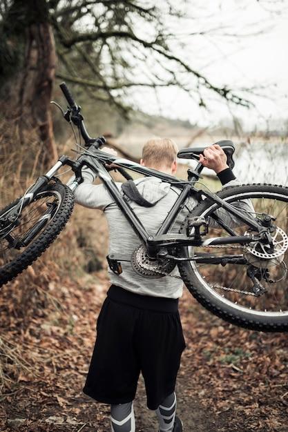 Homme portant un vélo de sport sur le dos, marchant dans la forêt Photo gratuit