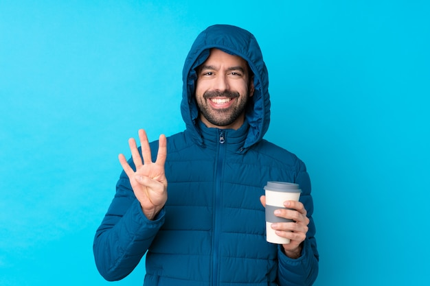Homme Portant Une Veste D'hiver Et Tenant Un Café à Emporter Sur Le Mur Bleu Isolé Heureux Et Comptant Quatre Avec Les Doigts Photo Premium