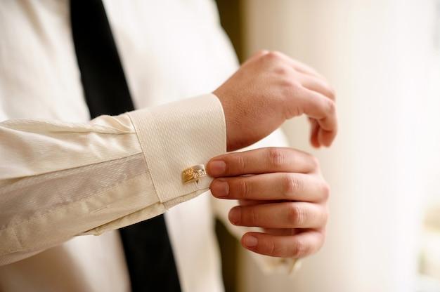 L'homme porte une chemise blanche et des boutons de manchette Photo Premium