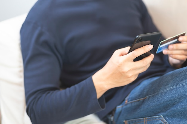 L'homme Porte Des Mains De T-shirt Bleu à L'aide De Smartphone Et De Carte De Crédit Sur Le Canapé à La Maison. Photo Premium