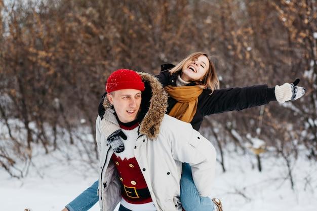Homme, porter, femme, dos, hiver, forêt Photo gratuit