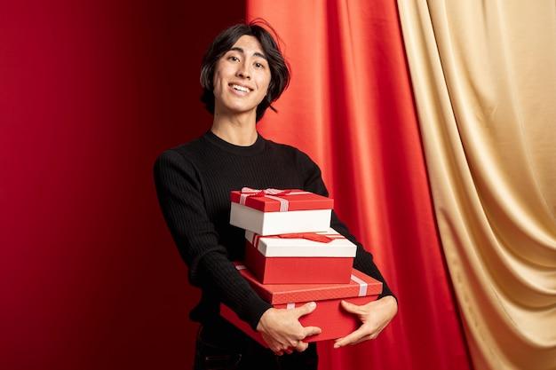 Homme posant avec des coffrets cadeaux pour le nouvel an chinois Photo gratuit