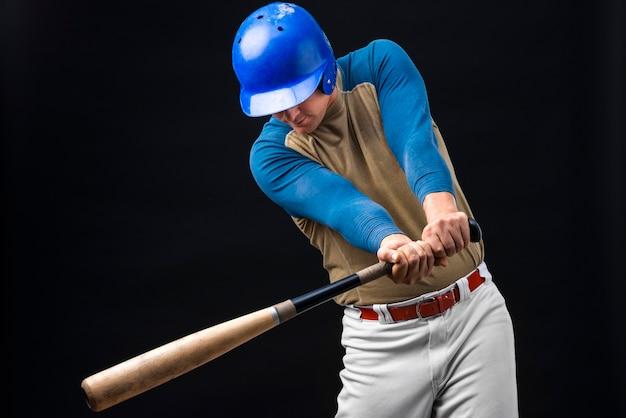 Homme Posant Dans Un Casque Avec Batte De Baseball Photo gratuit